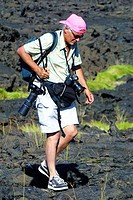 mature travel photographer carrying cameras