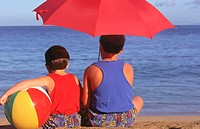 Boys on beach under umbrella