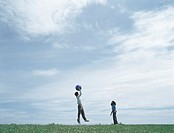 Young man and woman on grass in distance playing with ball, man jumping to catch ball