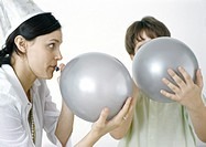 Woman and boy blowing up silver balloons