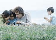 Man lying on grass with boy and girl looking at cellphone, second boy sitting apart