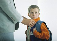 Man buttoning coat of boy with backpack