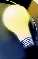 Close-up of yellow lightbulb on black surface