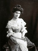 Young woman sitting in an elaborate dress,  1890s.