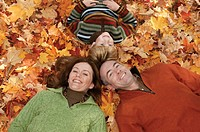 Family in pile of leaves, portrait