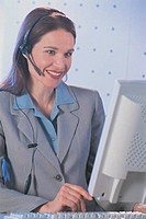 Woman with phone headset at computer