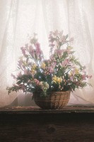 Flower arrangement in basket on windowsill