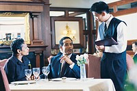 Couple in restaurant talking to waiter