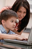 Woman talking on phone and helping son with laptop