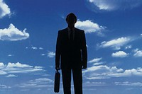 Silhouette of businessman against a blue sky