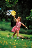 Young girl running outside with bubble toy