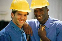 Business professionals wearing hard hats, portrait