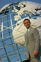 Business man holding a briefcase, standing in front of globe, portrait