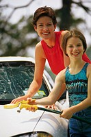 Mother and daughter washing car
