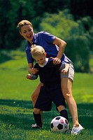 Mother playing soccer with son