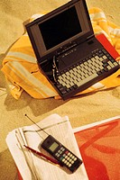Laptop, cell phone and newspaper on beach