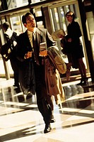 Businessman walking through sunlit lobby