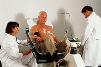 Doctors give stress test to mature male patient using an ergometer