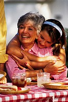 Mature woman at picnic table being hugged by granddaughter.