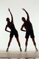 Silhouette of man and woman stretching