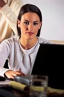 Businesswoman working on laptop computer, portrait.