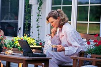 Woman sitting outside on patio working on laptop computer.