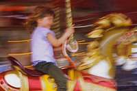 Girl on carousel horse, blurred motion