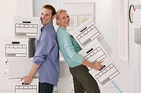 Business team moving boxes, portrait