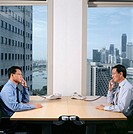 Two businessmen using telephones