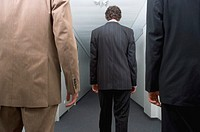 Three businessmen standing in corridor