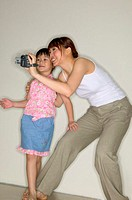 Mother and daughter using video camera