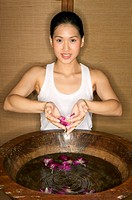 Woman lifting petals from bowl of water