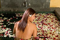 Woman in bath with petals