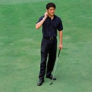 Man on golf green with bluetooth headset
