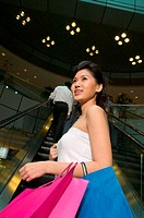 Woman with shopping bags on escalator
