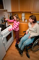 Disabled mother and daughter in kitchen