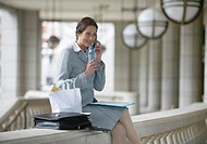Businesswoman Sitting on a Stone Railing Using a Mobile Phone