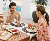 Mature Couple Sit Face-to-Face Over Breakfast at a Patio Table Laughing