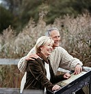 Senior Couple Leaning on a Fence in a Field