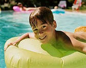 Smiling Young Boy Lying on an Airbed in a Swimming Pool