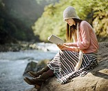 Woman Sat on a Boulder by a River, Reading a Book