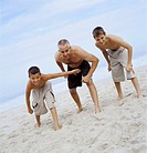 Father and Two Sons Standing in Start Positions on a Beach