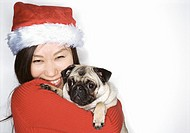 Portrait Shot of a Young Girl Wearing a Santa Hat and Holding a Pug Dog