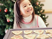 Young Girl Stands by a Christmas Tree With a Tray of Cookies, Looking Up and Laughing