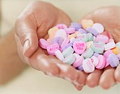 Close-up of a Person Holding a Pile of Heart-shaped Love Sweets
