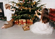 Two Children Sit on the Floor in a Living Room Decorating a Christmas Tree