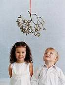 Portrait of a Young, Well-Dressed Boy and Girl Standing Under Mistletoe, the Boy Looking Upwards