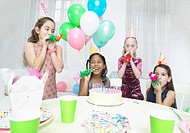 Four Girls in Party Hats Blowing Party Horns at a Table With a Birthday Cake