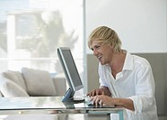 Man Sits at a GlassTable Using His Computer