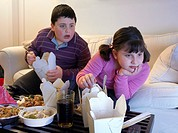 Overweight Brother and Sister Sitting Side by Side on a Sofa Eating Takeaway Food and Watching the TV